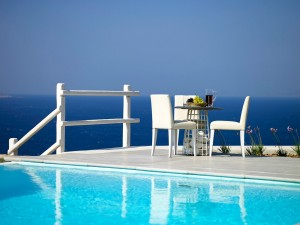 Chairs and a table at an amazing spot by the pool, offering a wonderful panoramic view of the Aegean