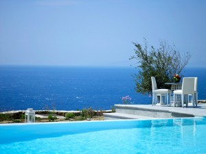 View of the blue Aegean sea as seen from a table by the private pool of the Mykonos Ammos Villa .