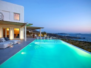 The Mykonos Ammos Villa private pool and lounge area during sunset with a view of Houlakia.
