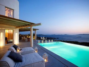Two lounge chairs by the private pool of the the luxury Mykonos Ammos Villa overlooking Houlakia
