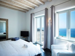 Inside one of the Mykonos Ammos Villa bedrooms equipped with flat screen TV, armchairs and sea view.