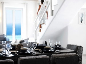 The Mykonos Ammos Superior Villa Dining table can accommodate up to 8 people and offers a sea view.