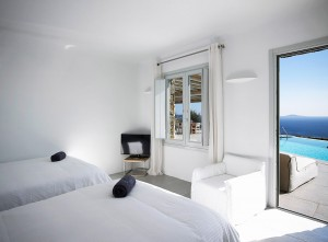 One of the Mykonos Ammos Villa bedrooms with a window and access to the private pool with sea view.