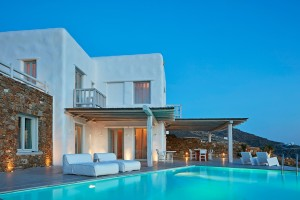 Exterior of the Mykonos Ammos Villa, private pool & outdoor lounge area in Houlakia, Mykonos at dusk