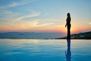 A lady gazes at the view of the sunset over the sea from beside the Mykonos Ammos Villa private pool