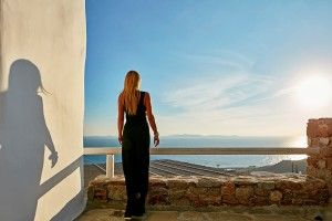 A woman stands looking at the view of the sea from outside the Mykonos Ammos Villa in Houlakia