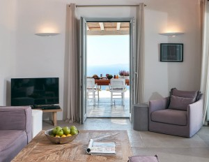 Ammos Villa living room with TV, chair, coffee table & balcony doors to Aegean sea view in Mykonos