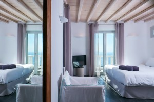 Mykonos Ammos Villa bedroom with mirror, chair, TV, bed & doors to balcony with sea view in Houlakia