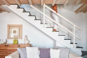 Man descends the stairs into the living room at the luxury Villa at Mykonos Ammos Villas in Houlakia