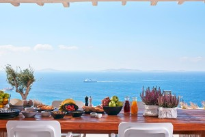 Food & drink on the outdoor dining table at the luxury Mykonos Ammos Villa with a view of the sea