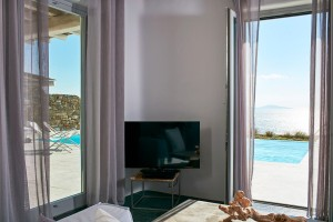 TV & sofa in Mykonos Ammos Villa living room. View of private pool & Aegean sea through patio doors