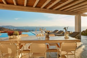 Wine on dining table on Superior Villa sea view veranda beside the private pool in Houlakia, Mykonos