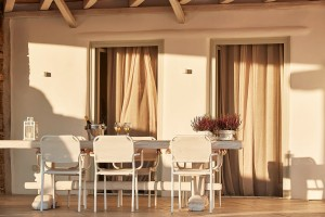 Outdoor veranda & dining table in front of open patio doors of Mykonos Ammos luxury Superior Villa