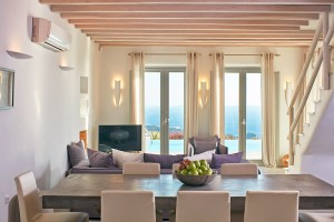 Superior Villa in Mykonos living room with patio doors to sea view & private pool. Table, sofa & TV.
