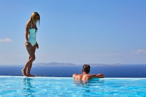 Man admires the sea view from Superior Villa private pool in Mykonos. Woman stands above him.