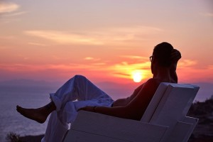 Man in chair gazes at view of the sunset over the sea from pool area of Superior Villa in Mykonos